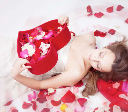Beautiful girl with rose petals in heart form box Stock Photo - 12326246