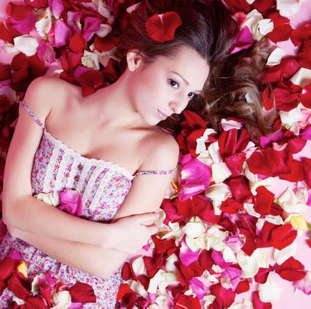 Beautiful girl with rose petals photo