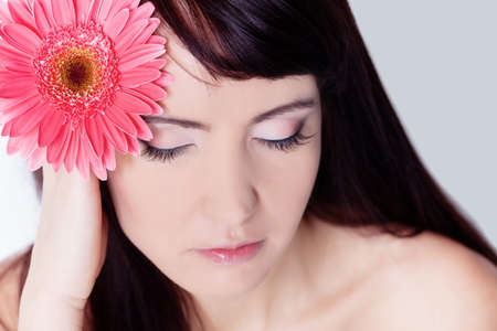 Girl with gerbera flower in studio photo