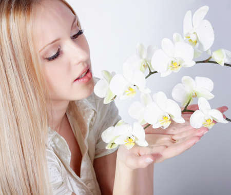 Girl with white orchid in studio photo