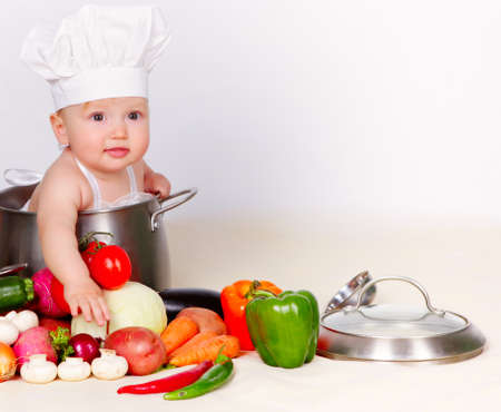 Baby cook with vegetables in studio Stockfoto