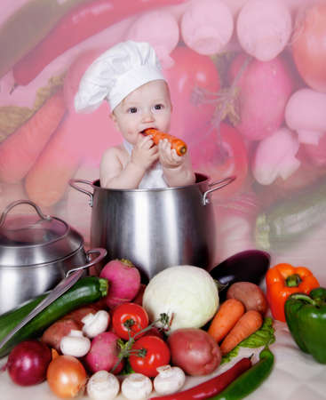 funny tomatoes: Baby cook with vegetables in studio Stock Photo