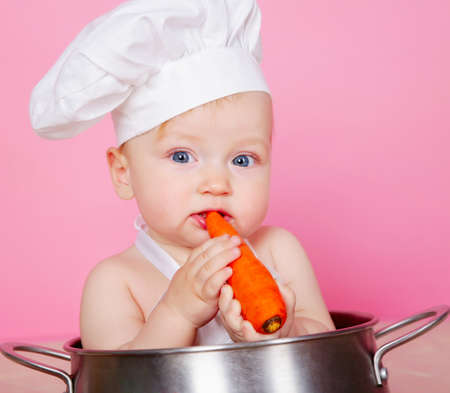 Baby cook eating carrot in studio photo