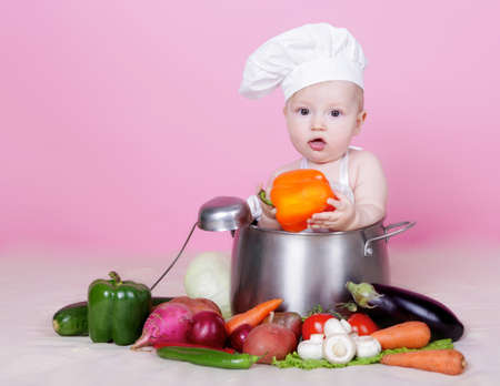 Baby cook with vegetables in studio photo