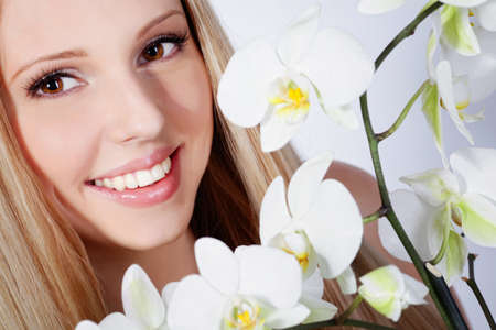 Beautiful blond girl with orchid flower in studio photo