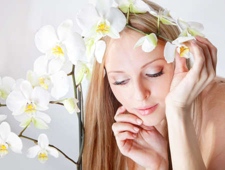 Beautiful blond girl with orchid flower in studio Stock Photo - 12604155