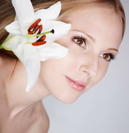 Beautiful blond girl with lily flower in studio Stock Photo - 12604002