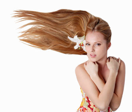 Beautiful blond girl with lily flower in studio photo