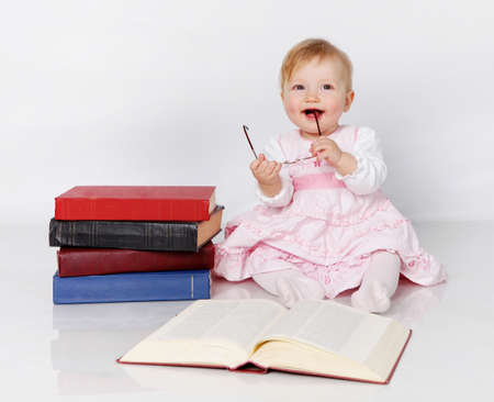 Little girl near the books with glasses in hands photo