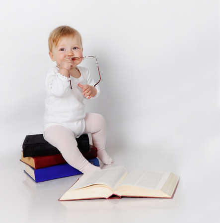 Little girl sitting on the books with glasses in hands photo