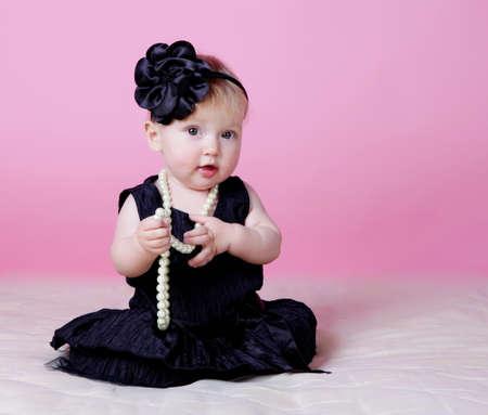 Little girl holding beads in hands