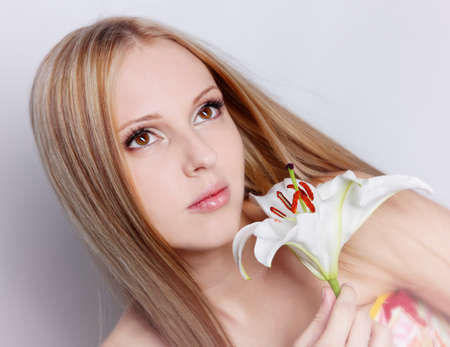 Beautiful blond girl with lily flower in hand Stock Photo - 12604414