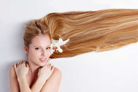 Beautiful blond girl with lily flower in hair photo