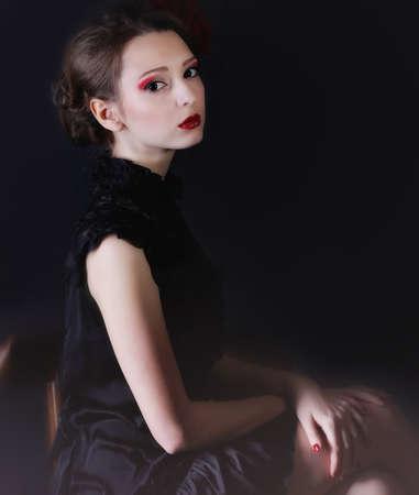 Beauriful smiling girl black dress sitting in studio