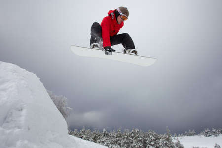 Snowboarder in red clothes jumping from springboard