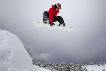 Snowboarder in rode kleren springen van springplank