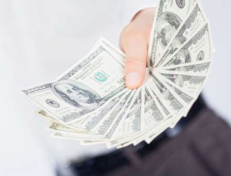 punhado: A man showing a handful of dollars.