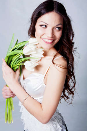 Beauriful brunette girl with tulip flowers in studio photo