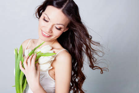 Beauriful brunette girl looking tulip flowers in studio Stock Photo - 12604559