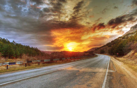 Asphalt road and evening sun in clouds photo