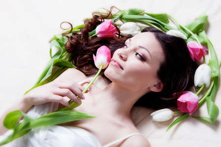 womens day: Beauriful brunette girl laying in bed with tulip flowers Stock Photo