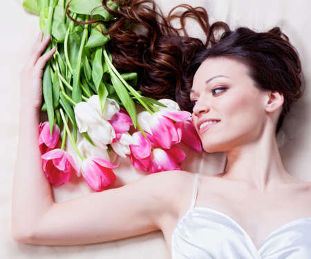 Beauriful brunette girl laying in bed with tulip flowers photo