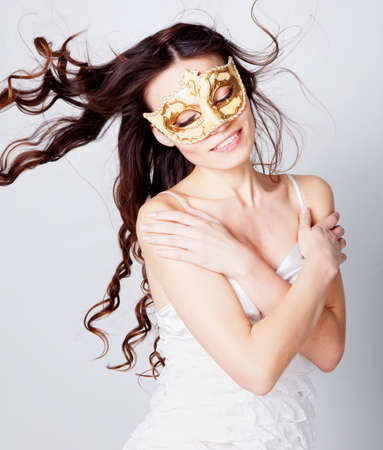 Beautiful brunette girl in masquerade mask photo