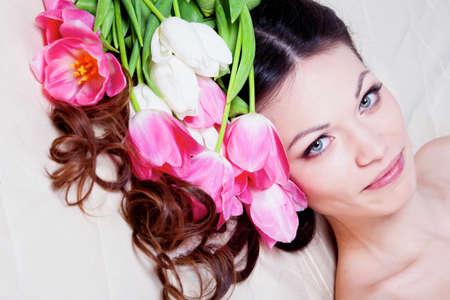 Hermosa chica morena en la cama con flores de tulip�n Foto de archivo - 12604611