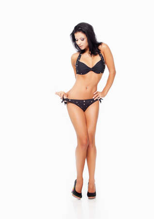 young bikini: Girl in black swimsuit isolated on white