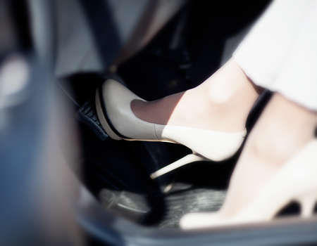 A woman's foot depressing the brake pedal of a car. photo