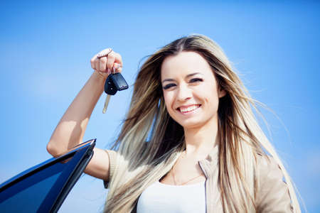 car dealers: Beautiful girl with car key in hand