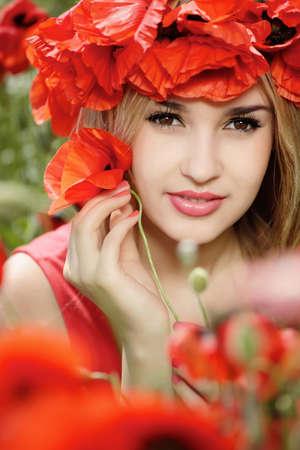 campo de flores: bella rubia en una corona de flores de amapola