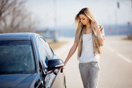 Young woman opening her car photo