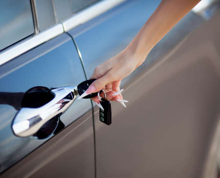 key to freedom: mano de la mujer de apertura con llave la puerta del coche Foto de archivo