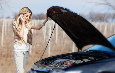 Beautiful blond girl calling cellphone near her broken car