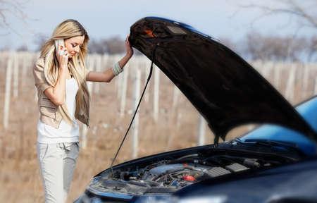Beautiful blond girl calling cellphone near her broken car