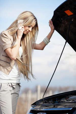 broken car: Beautiful blond girl calling cellphone near her broken car
