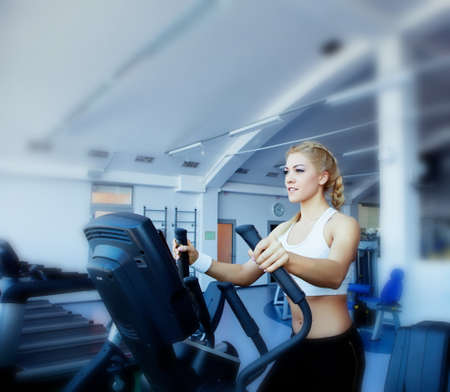 Beautiful girl in fitness center on running track photo