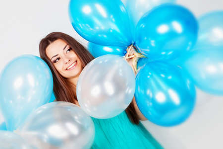 Beautiful brunette girl in studio with balloons on white background  photo