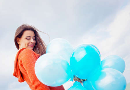 Girl with balloons under blue sky with clouds photo
