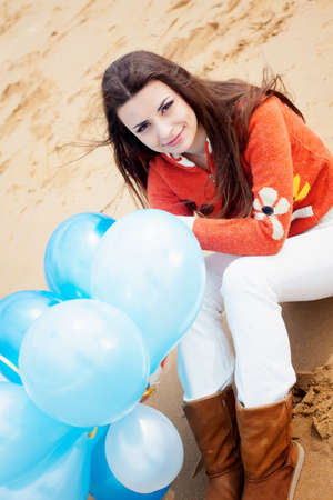 Girl on the beach with balloons in hand photo