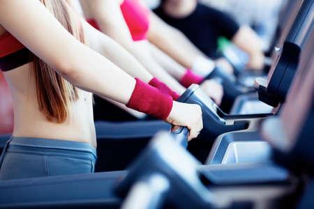 Vrouw de handen op het bijhouden van machine in fitnesscentrum