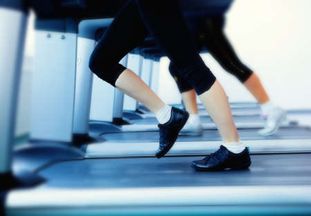 Woman legs on tracking machine in fitness center