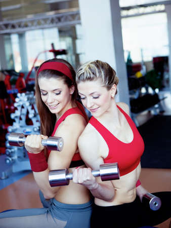 Two girls with dumbbells in hahds  photo