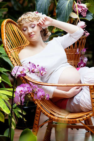 Beautiful pregnant woman sitting in garden photo