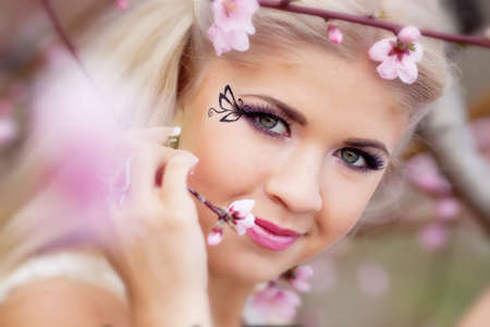 Beautiful blond girl in blossom garden photo