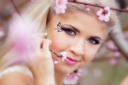 Beautiful blond girl in blossom garden photo