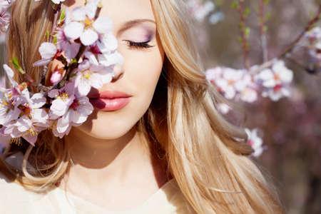 Beautiful blond girl in blossom garden