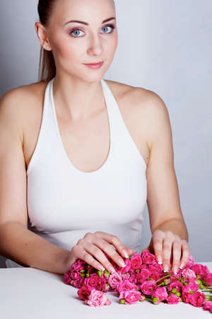 handcare: Beautiful woman with hands on the rose flowers Stock Photo