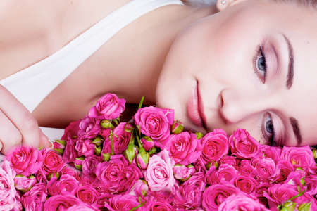Beautiful girl face near the rose flowers photo